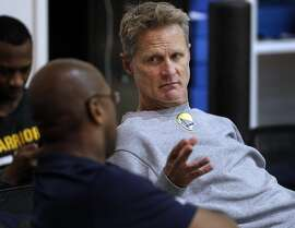 Warriors head coach Steve Kerr chats with acting head coach Mike Brown during practice at the Warriors headquarters in Oakland, Calif., on Thursday, May 25, 2017.