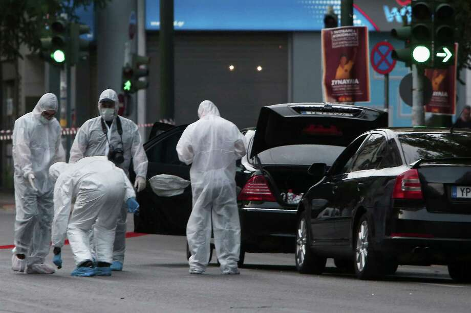 Police search for evidence at the scene of an explosion in Athens on Thursday. The blast injured former Prime Minister Lucas Papademos, but the injuries were not thought to be life-threatening. Photo: ANGELOS TZORTZINIS, Stringer / AFP or licensors