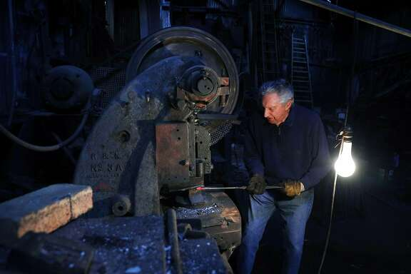 Tony Rosellini works on a manhole cover hook at Edwin Klockar's Blacksmithing Shop in San Francisco, Calif., on Wednesday, May 24, 2017.  The shop is a piece of the last working bit of old Rincon Hill, a blacksmith shop on Folsom Street. It's a city landmark, with dirt floors in the back. But Tony Rosellini, the blacksmith is 87 years old, and its fate is in the air. Travis Kelly, his grandson, is rethinking the place.