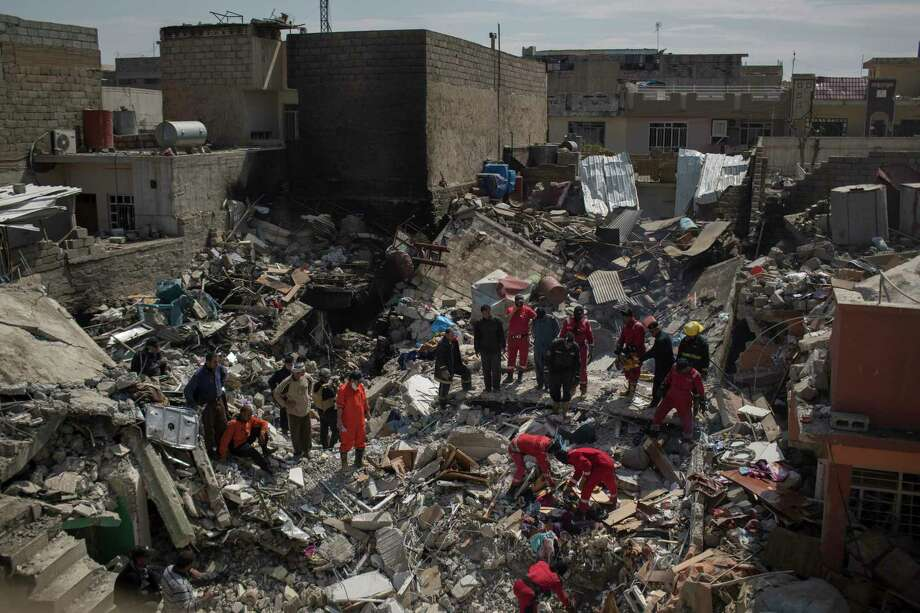 FILE - Civil protection rescue teams search through the debris of a house destroyed in a March 17 U.S. airstrike in the western sector of Mosul in this file photo from Friday, March 24, 2017. The strike killed more than 100 civilians who were taking refuge from fighting. Residents of western Mosul describe a brutal battlefield where terrified families scurry from house to house, trying to find safe refuge as increasingly heavy airstrikes and artillery level buildings and IS militants prevent people from fleeing the city. (AP Photo/Felipe Dana, File) ORG XMIT: CAI304 Photo: Felipe Dana / Copyright 2017 The Associated Press. All rights reserved.