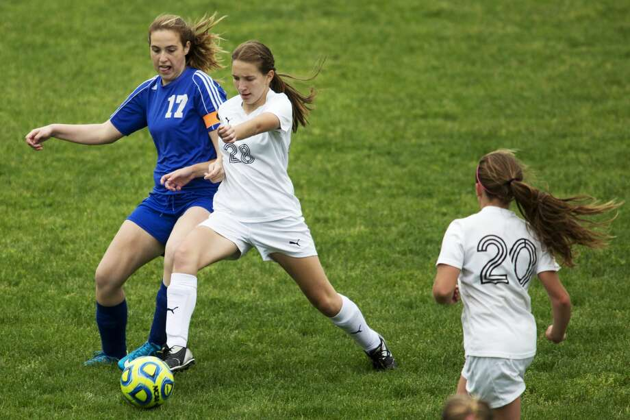 Oscoda's Kaleigh Vollmers and Bullock Creek's Emma Fransen fight for possession of the ball in a game at Bullock Creek High School on Thursday. Photo: Theophil Syslo