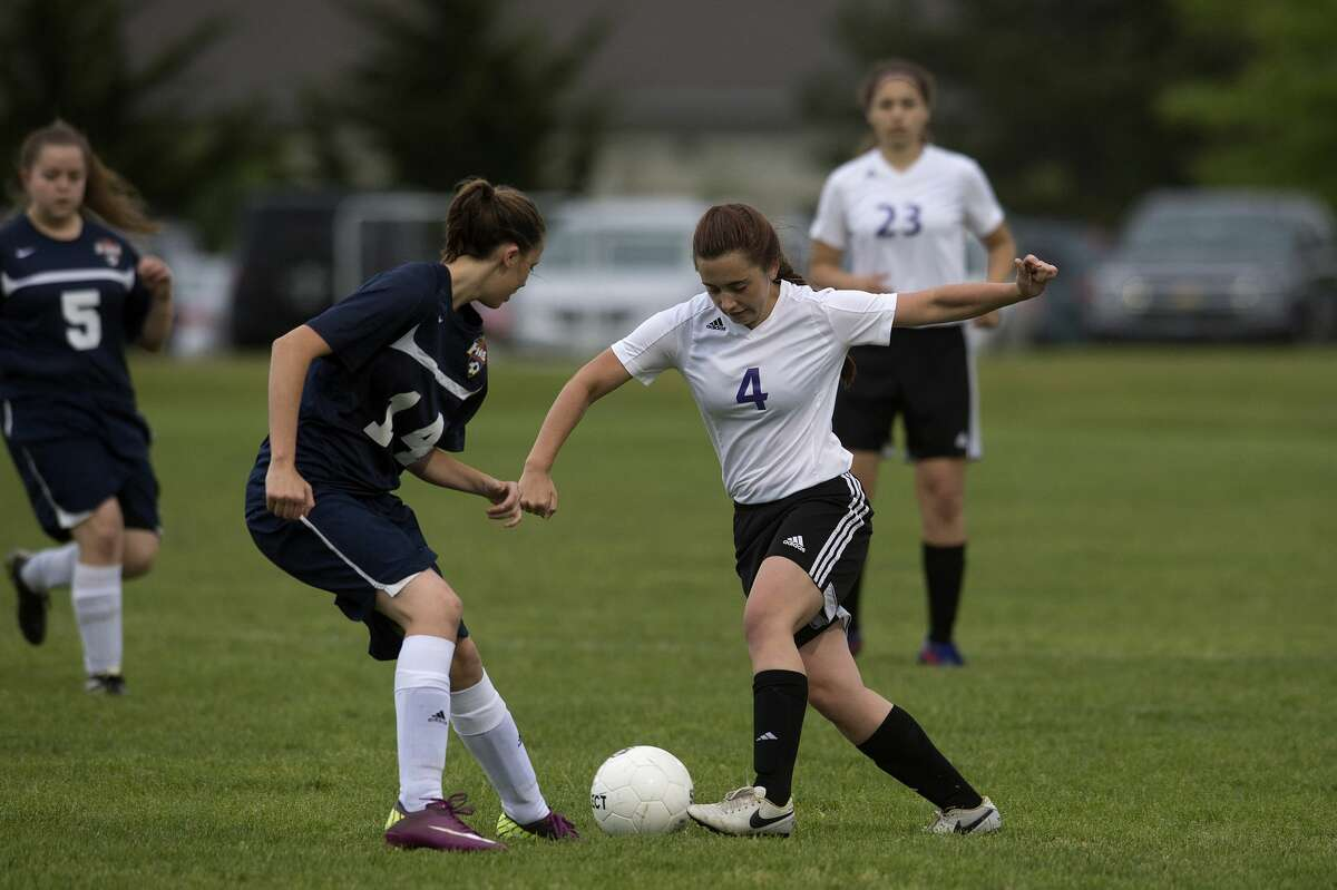 Calvary Baptist Academy's Brienna Schmidt dribbles around Immanuel Christian's Hannah Phillips fight for control of the ball during the first half of the semi-final girls' soccer tournament Thursday afternoon.