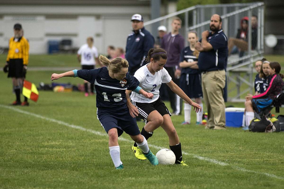 Calvary Baptist Academy's Caroline Holderman, right, and Immanuel Christian's Avery Gibson fight for control of the ball during the first half of the semi-final girls' soccer tournament Thursday afternoon.