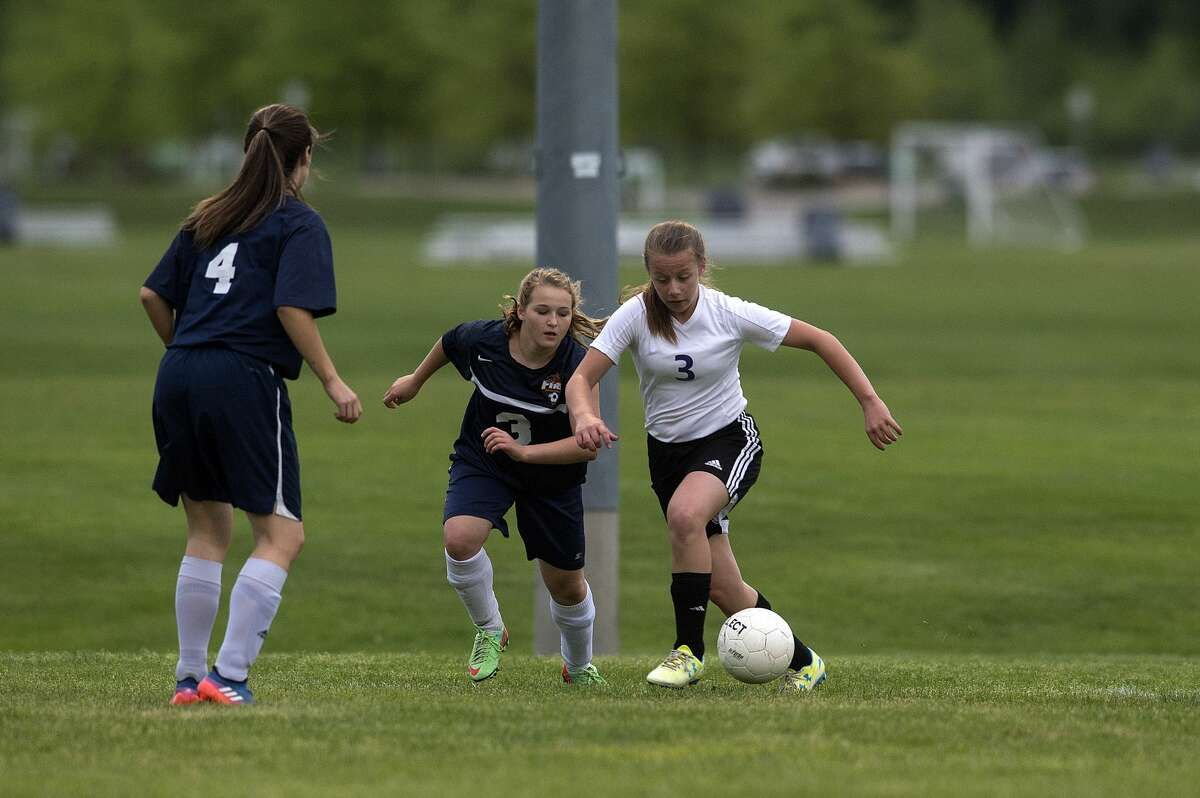 Calvary Baptist Academy's Courtney Warner, right, and Immanuel Christian's Emily Gibson during the first half of the semi-final girls' soccer tournament Thursday afternoon.