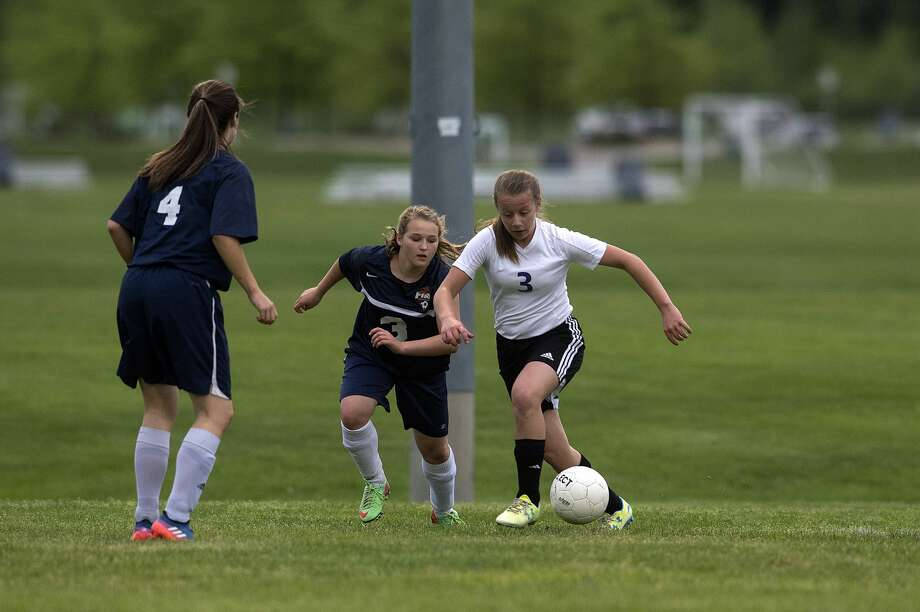 Calvary Baptist Academy's Courtney Warner, right, and Immanuel Christian's Emily Gibson during the first half of the semi-final girls' soccer tournament Thursday afternoon. Photo: Brittney Lohmiller/Midland Daily News/Brittney Lohmiller