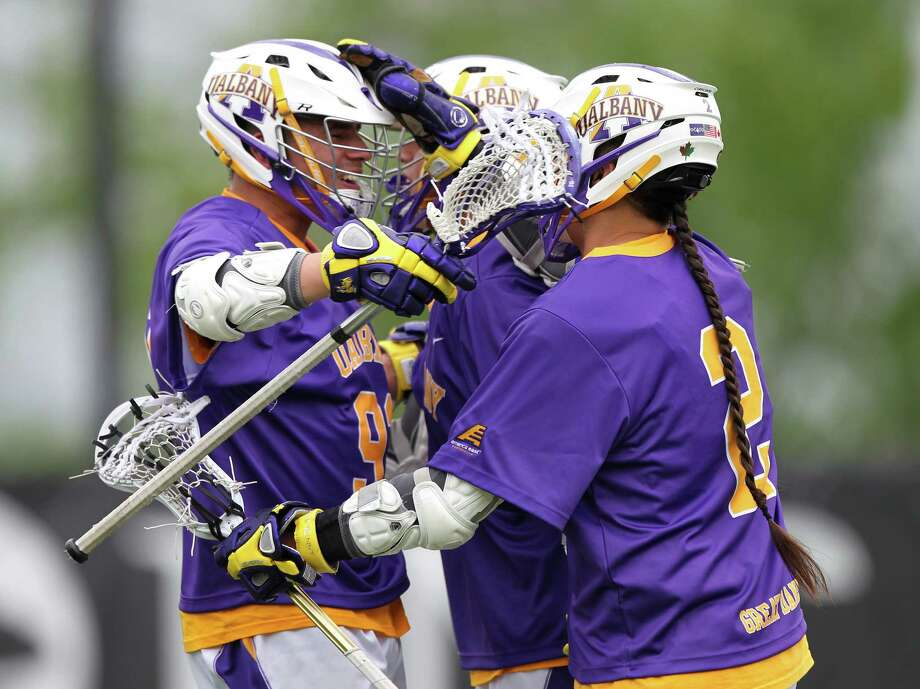 UAlbany players Ty Thompson, left, Lyle Thompson, center, and Miles Thompson celebrate after a goal against Loyola on Saturday, May 11, 2014, in their men's lacrosse NCAA Tournament first-round game at Ridley Athletic Complex in Baltimore. (Brian Schneider / www.ebrianschneider.com) Photo: Brian Schneider / Brian Schneider