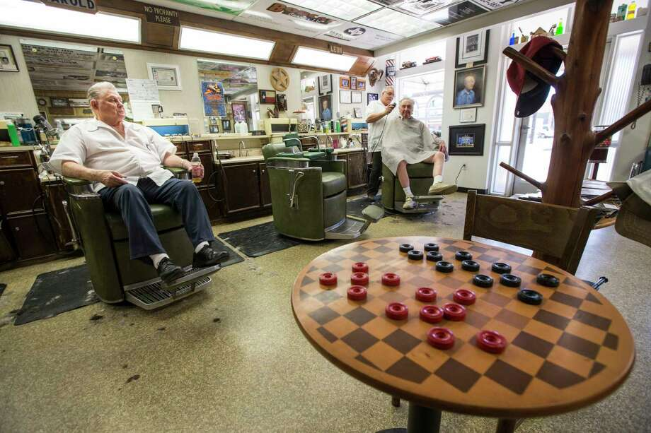 Barber Darold Vandewerker, left, sits in a barber's chair as Leon Apostolo, far right, cuts Roland Furstenfeld's hair in Shepard's Barber Shop on Thursday, May 25, 2017, in Conroe. Between 2015 and 2016, Conroe was the fastest-growing large city (population of 50,000 or more) at 7.8 percent, making its growth rate 11 times the nation's growth rate . Photo: Brett Coomer, Staff / © 2017 Houston Chronicle