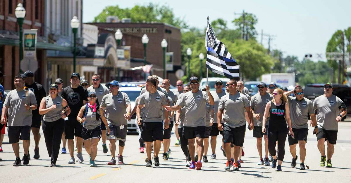 Law enforcement officers jog through downtown Conroe in a run to benefit the Special Olympics. Keeping a small-town sensibility while managing growth requires a balancing act, officials admit.