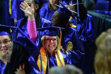 Joanne Elizabeth Gorlo, of Stratford, waves to her husband Brian and the rest of her family as she enters in the procession for Housatonic Community College's Commencement 2017 at the Webster Bank Arena in Bridgeport, Conn., on Thursday May 25, 2017. With 612 graduates, this is the college's 3rd largest graduating class in its history.