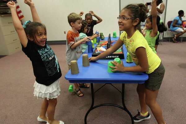 Ainsley Tarver, 7, left, reacts as she wins a round of stacking against Liyah Babineau, 7, right,  during the Sport Stacking tournament at the Harris County Octavia Fields Branch Library, Monday, July 29, 2013, in Humble. ( Karen Warren / Houston Chronicle )