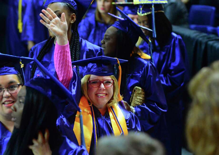 Joanne Elizabeth Gorlo, of Stratford, waves to her husband Brian and the rest of her family as she enters in the procession for Housatonic Community College's Commencement 2017 at the Webster Bank Arena in Bridgeport, Conn., on Thursday May 25, 2017. With 612 graduates, this is the college's 3rd largest graduating class in its history. Photo: Christian Abraham / Hearst Connecticut Media / Connecticut Post