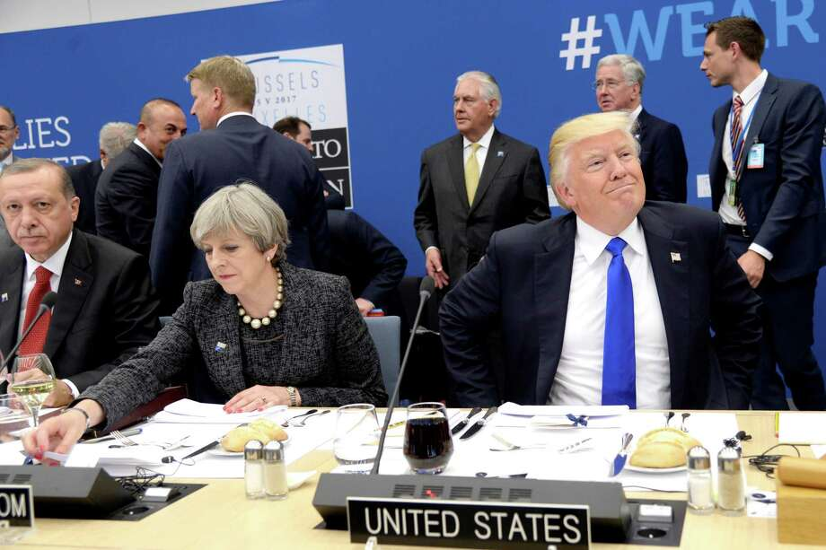 US President Donald Trump, right,  reacts as he sits next to Britain's Prime Minister Theresa May, centre and Turkish President Recep Tayyip Erdogan as they participate in a working dinner meeting, during the NATO summit of heads of state and government, at the NATO headquarters, in Brussels on Thursday, May 25, 2017. US President Donald Trump inaugurated the new headquarters during a ceremony on Thursday with other heads of state and government. (Thierry Charlier/Pool Photo via AP) ORG XMIT: LON180 Photo: Thierry Charlier / afp or licensors
