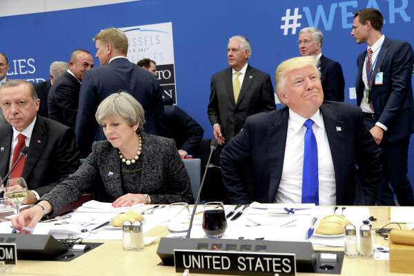 US President Donald Trump, right,  reacts as he sits next to Britain's Prime Minister Theresa May, centre and Turkish President Recep Tayyip Erdogan as they participate in a working dinner meeting, during the NATO summit of heads of state and government, at the NATO headquarters, in Brussels on Thursday, May 25, 2017. US President Donald Trump inaugurated the new headquarters during a ceremony on Thursday with other heads of state and government. (Thierry Charlier/Pool Photo via AP) ORG XMIT: LON180