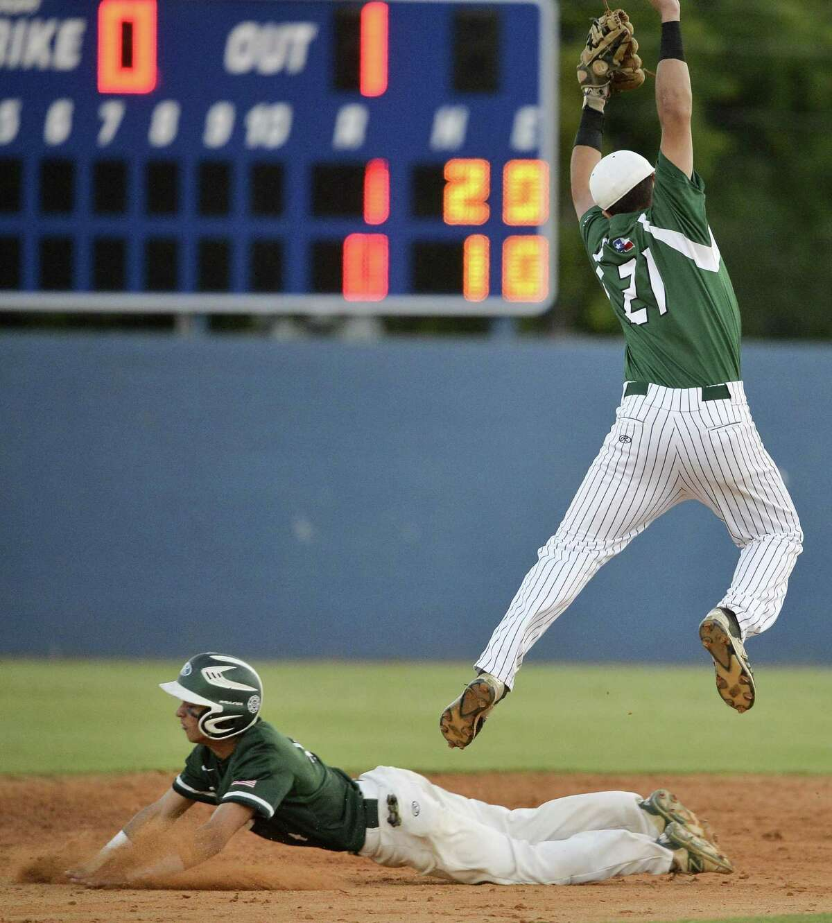 Southwest's Gabe Rivera, left, steals second base as Reagan's Ramon Garza jumps to avoid a collision during game one of their Region IV-6A semi-final playoff baseball series, Thursday, May 25, 2017, at SAISD Sports Complex in San Antonio. Reagan won 9-1. (Darren Abate/For the Express-News)