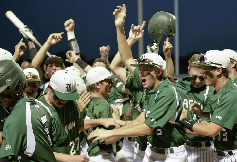 Reagan players celebrate a run during Game 1 of their Region IV-6A semifinal playoff baseball series against Southwest on May 25, 2017, at SAISD Sports Complex in San Antonio. Photo: Darren Abate /For The Express-News / San Antonio Express-News