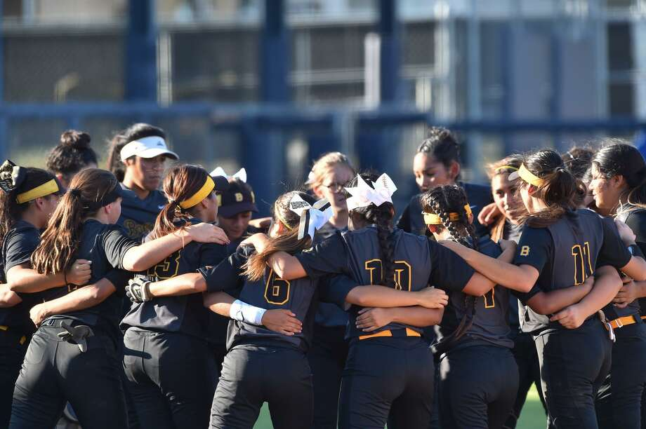 The Brennan Bears softball team lock arms before their Region IV-6A regional final series versus New Braunfels Canyon at St. Mary's University Thursday evening. Photo: Robin Jerstad, Freelance / San Antonio Express-News / ROBERT JERSTAD