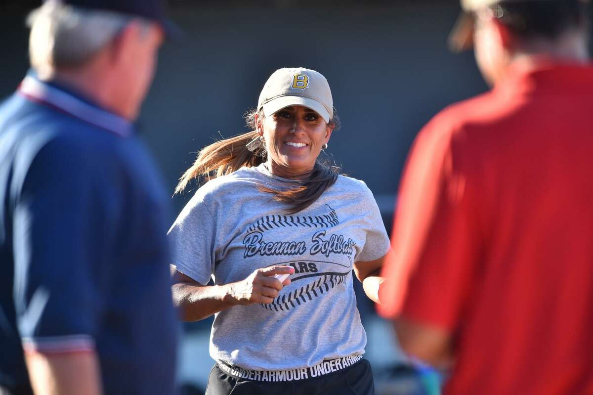 Brennan Bears softball coach Ruby de la Garza smiles as she heads to home plate prior to the Region IV-6A regional final series against New Braunfels Canyon at St. Mary's University on May 26, 2017.
