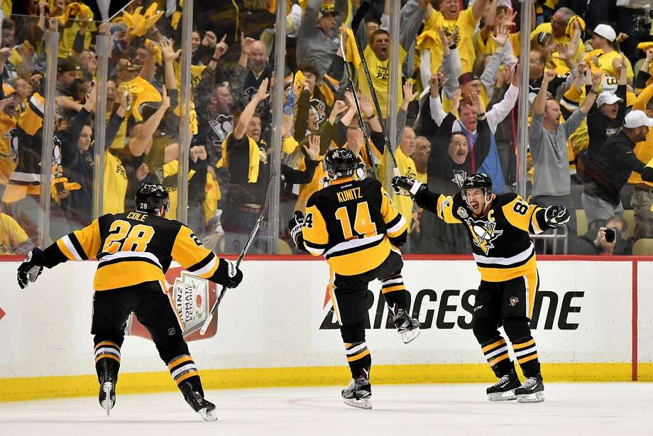 Chris Kunitz celebrates with Ian Cole and Sidney Crosby after scoring in the second overtime. Photo: Jamie Sabau, Getty Images