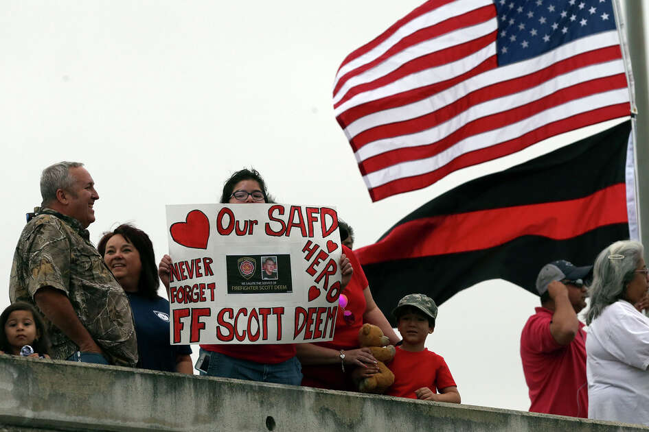 People honor a procession of firefighting vehicles moves north Friday May 26, 2017 on US Highway 2812 North in honor of fallen San Antonio firefighter Scott Deem who died battling a fire last week.