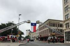The Texas state flag hangs from the ladders of two San Antonio Fire Department trucks on Alamo Street ahead of the funeral procession for Scott Deem on May 26, 2017.