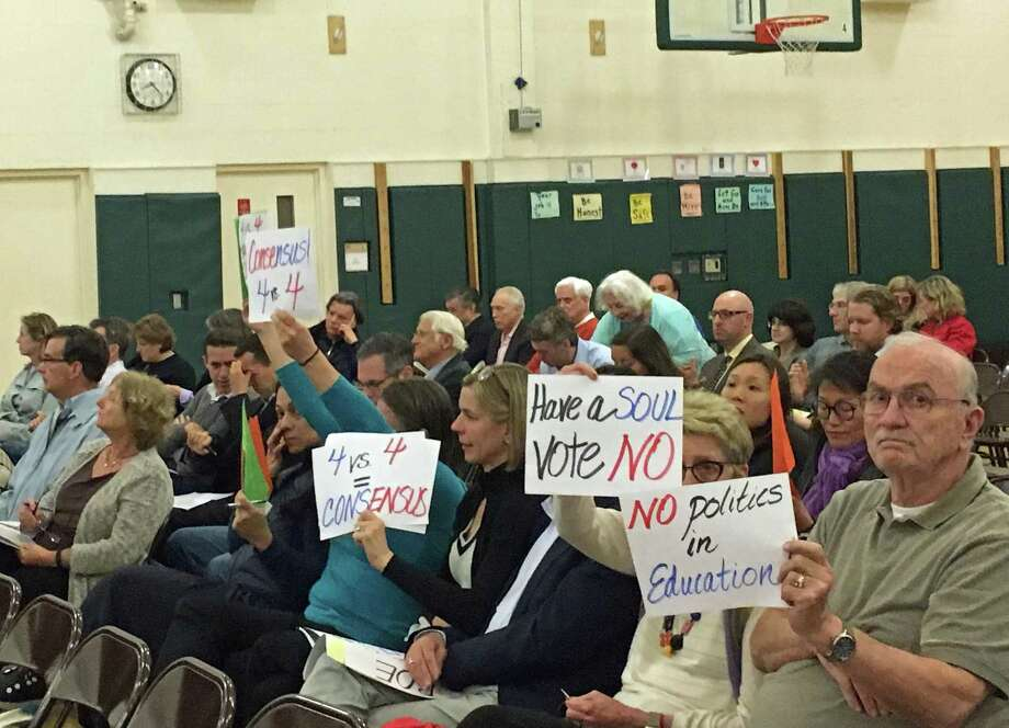 Community members brought signs to Thursday's school board meeting, indicating their opinions on the proposal to change the Board of Education's election structure. Photo: Emilie Munson