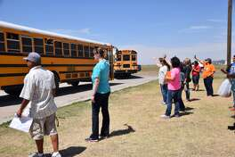 Teachers and staff of Hillcrest Elementary wave goodbye as school buses loaded with students pull away from the campus Thursday on the last day of school. A sincere wave goodbye at the start of summer vacation is a longstanding tradition at the school.
