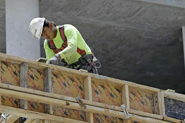 A construction worker works on an apartment high-rise in Miami. The gross domestic product — the broadest gauge of the economy — expanded in the January-March quarter at a 1.2 percent annual rate, the government said Friday.