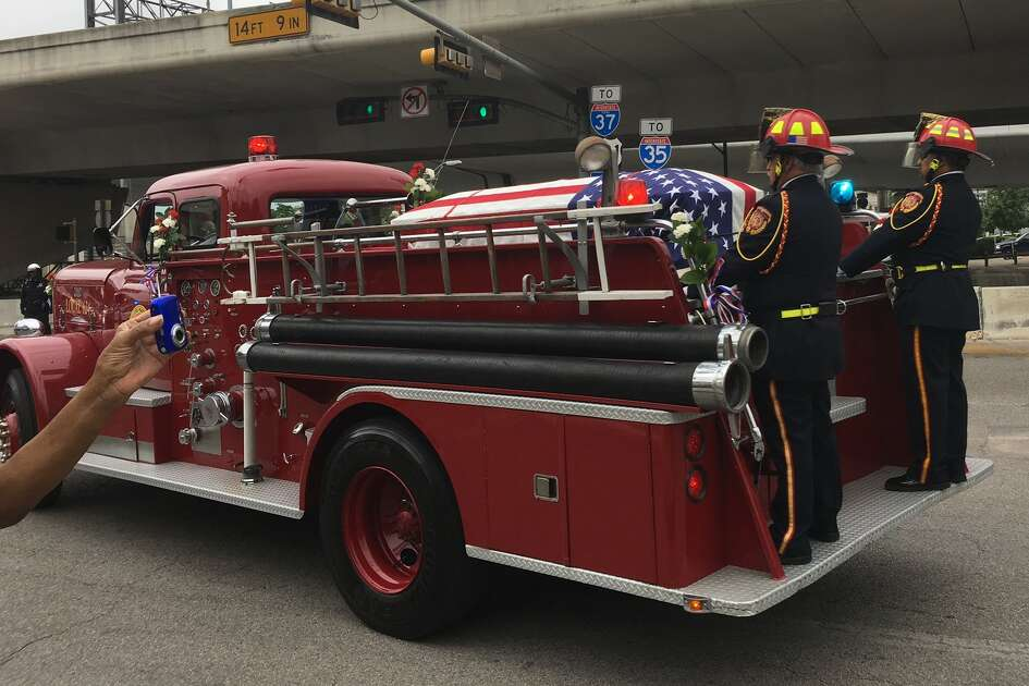 Fire truck bearing firefighter Scott Deem's casket leads funeral procession toward the Alamo.