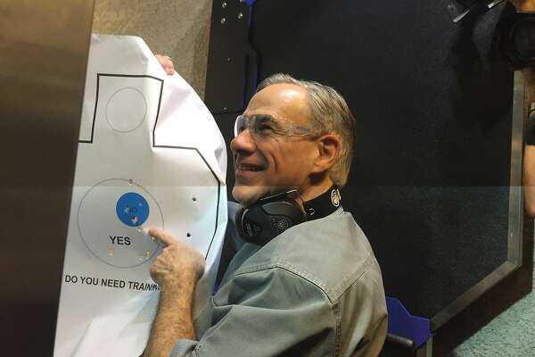 "Gov. Greg Abbott holds up the target he had just fired at Friday after signing a bill that will reduce the cost of gun licenses. Surrounded by reporters and cameras, Abbott then joked, ""I'm going to carry this around in case I see any reporters."" The media there laughed but when it went out on social media, there was immediate adverse reaction."