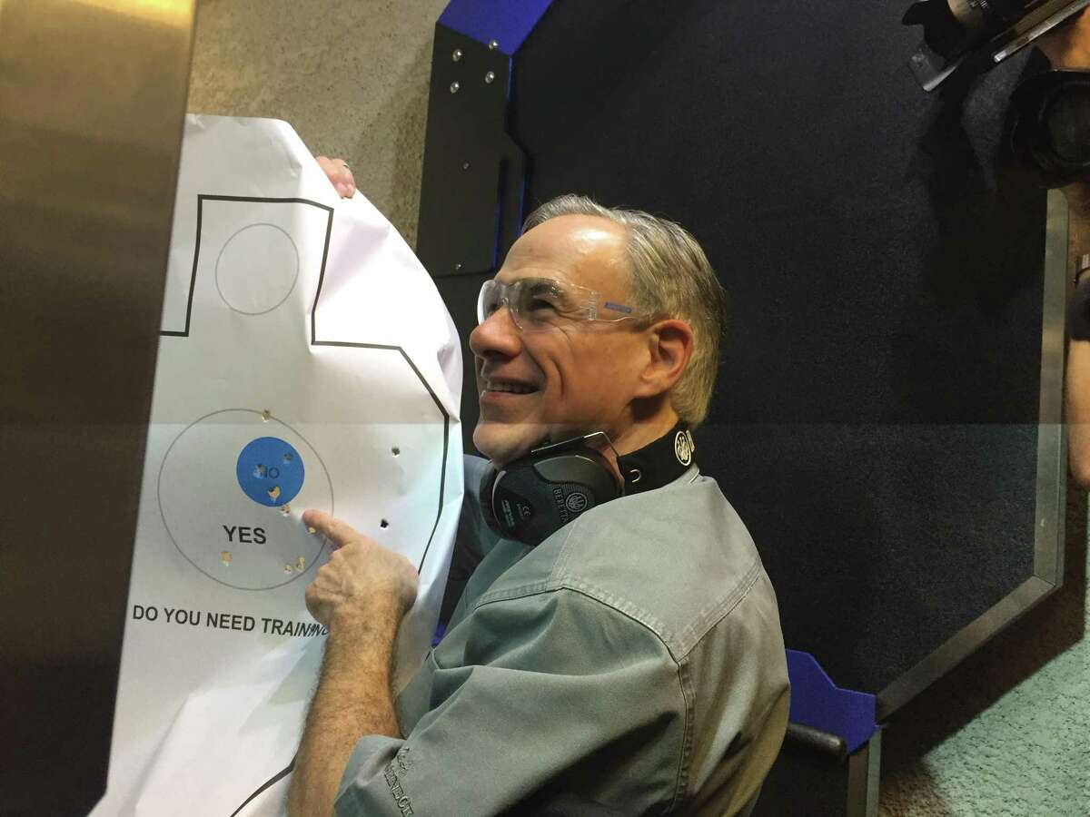 Gov. Greg Abbott holds up the target he had just fired at Friday after signing a bill that will reduce the cost of gun licenses. Surrounded by reporters and cameras, Abbott then joked,