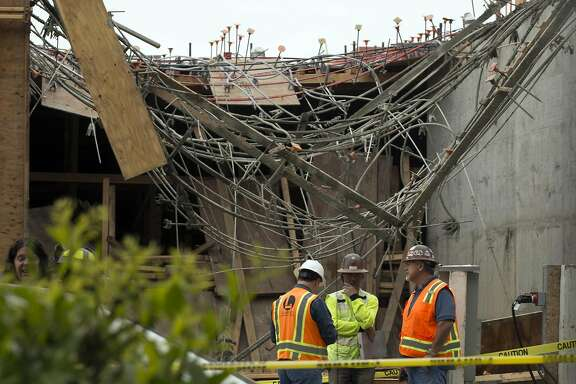 Emergency personnel and construction workers survey the aftermath of a building collapse at a construction site on 30th Street, on Friday, May 26, 2017 in Oakland, Calif.