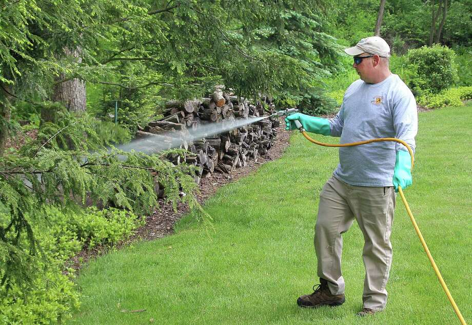 Don Fossi of Deer and Tick Guard in New Milford sprays a tick barrier around the perimeter of a yard in Brookfield, Conn., on Wednesday, May 24, 2017. Photo: Chris Bosak / Hearst Connecticut Media / The News-Times
