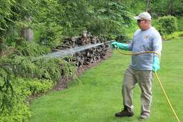 Don Fossi of Deer and Tick Guard in New Milford sprays a tick barrier around the perimeter of a yard in Brookfield, Conn., on Wednesday, May 24, 2017.