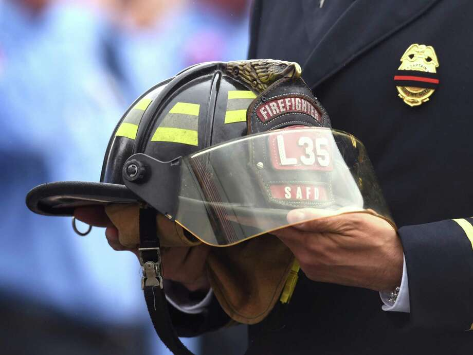 A helmet from Ladder 35 is carried in a procession to Community Bible Church for the funeral service of firefighter Scott Deem on Friday, May 26, 2017. Deem, who was a crewman on Ladder 35, died while fighting a fire at Ingram Square shopping center on May 18. Photo: Billy Calzada, Staff / San Antonio Express-News / San Antonio Express-News