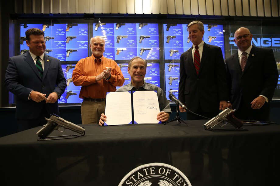 Texas Gov. Greg Abbott signs into law SB 16, which lowers the first-time fee for a license to carry a firearm to $40, a cut of $100. Additionally, the renewal fee has been lowered from $70 to $40. Pictured with Abbott are Senator Robert Nichols (R-Jacksonville), who represents Liberty and San Jacinto counties in Senate District 3. In addition to Nichols, the bill was authored by Senator Joan Huffman (R-Houston) and State Rep. Phil King (R-Weatherford). Photo: Submitted