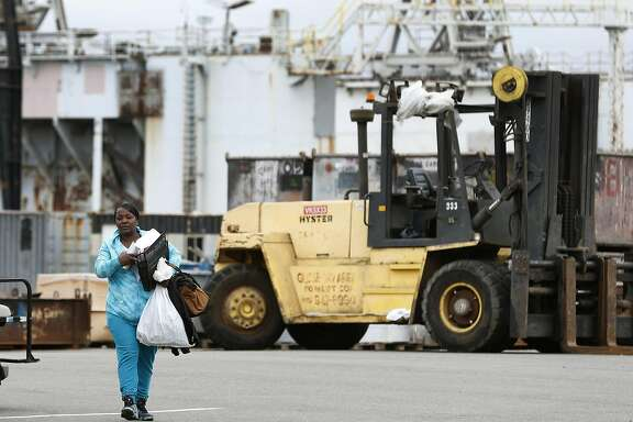 Carlisa Coleman carries the last of her belongings from where she worked for 18 years before she was laid off at the former BAE Systems shipyard at Pier 70 in San Francisco, Calif. on Friday, May 26, 2017. The shipyard and dry docks were acquired by Puglia Engineering but backed out of the deal when it claimed there were issues it inherited that were never disclosed.