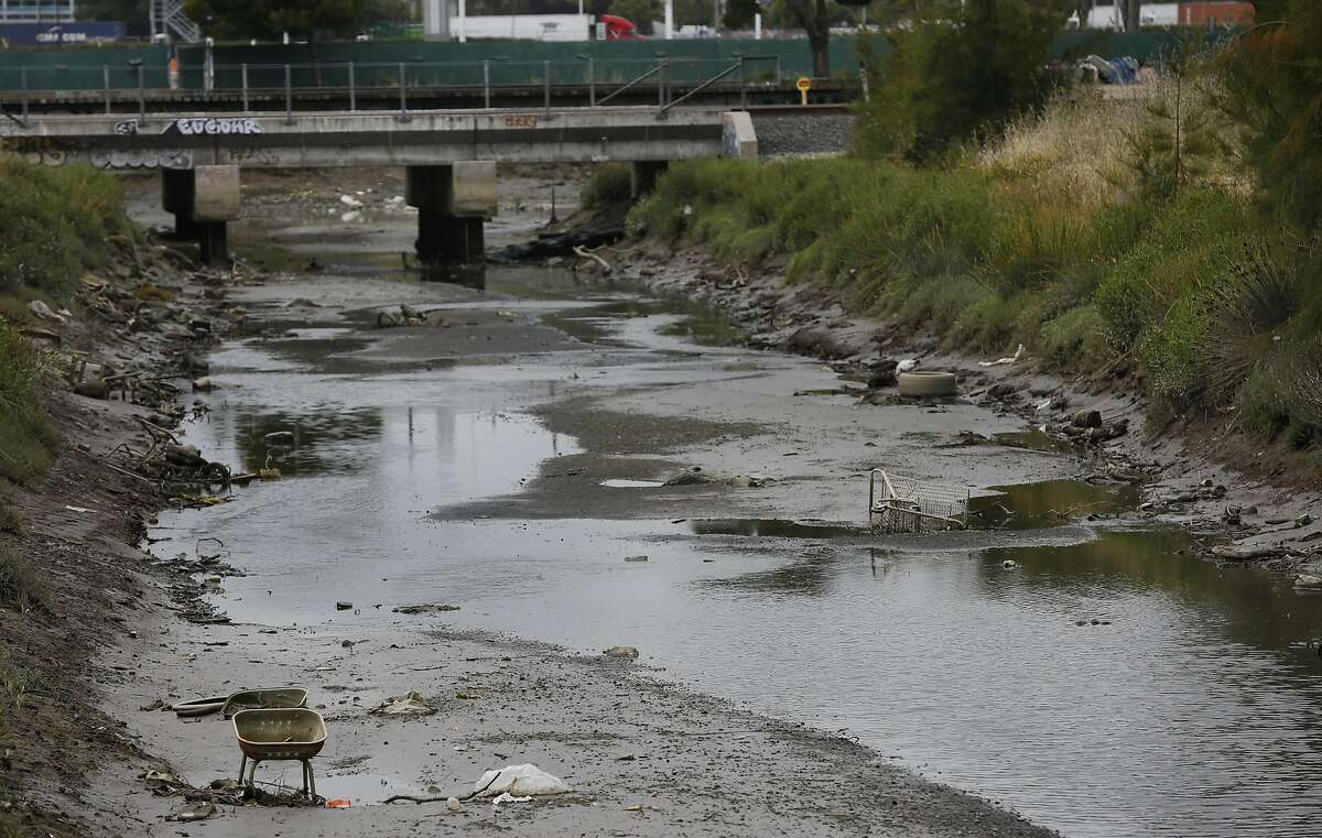 Trash and debris can be seen in Lion Creek, which empties into Damon Slough May 26, 2017 in Oakland, Calif.