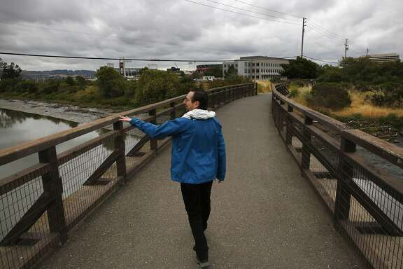 David Lewis, the Executive Director of Save the Bay, walks on a bridge over the Damon Slough while pointing out the trash problem for the Chronicle May 26, 2017 in Oakland, Calif.