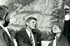 California's governor, Edmund G. Brown, points out one of the high Sierra peaks on August 18, 1962, to President Kennedy as secretary of Interior, Stewart L. Udall looks on. The president was given a tour of Yosemite scenic points before taking off by helicopter for San Luis Dam dedication. UPI photo