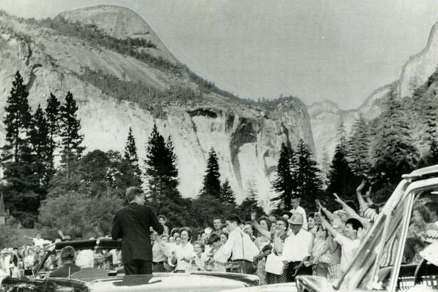 President John F. Kennedy is greeted by enthusiastic vacationers when he arrived in Yosemite National Park on August 17, 1962, for an overnight stay. Peak on the upper left is North Dome, Half Dome at 8,937 feet tall is on the upper right. UPI photo