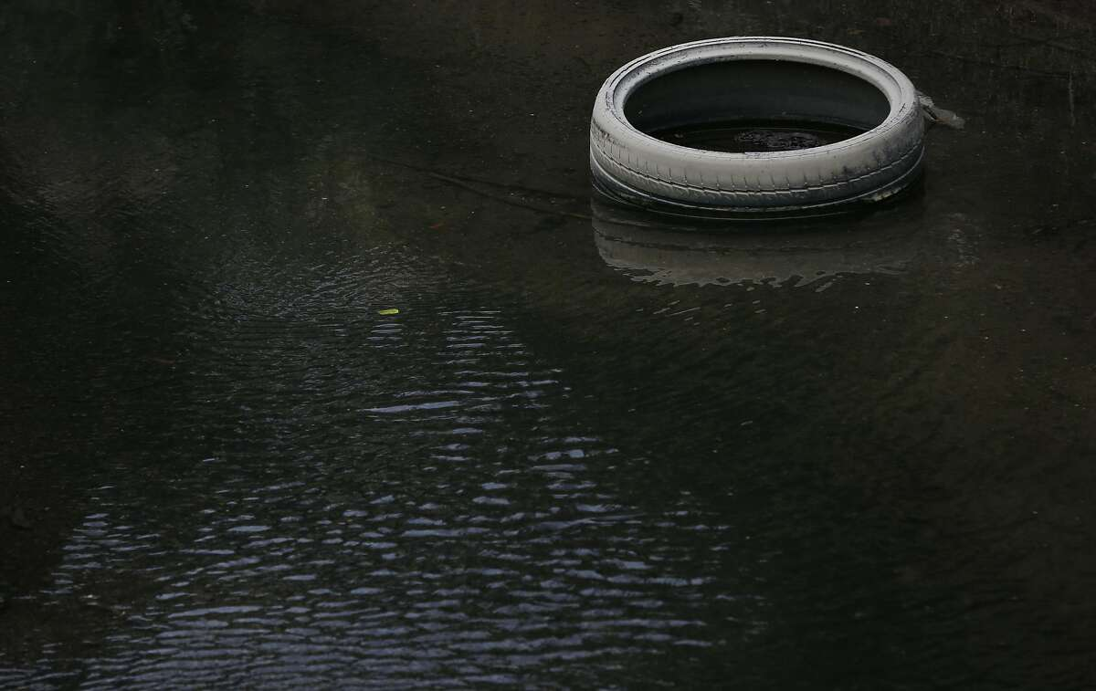 A car tire sits in Lion Creek, which empties into Damon Slough May 26, 2017 in Oakland, Calif.