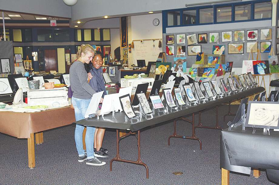 From left, Bad Axe seniors Maggie Ingram and Cher Sophannarat share a smile as they gaze over the hundreds of pieces of artwork featured at this year's Bad Axe Art Show. Photo: Bradley Massman/Huron Daily Tribune