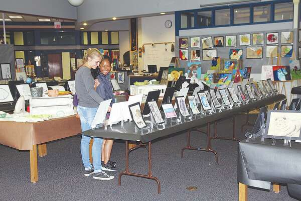 From left, Bad Axe seniors Maggie Ingram and Cher Sophannarat share a smile as they gaze over the hundreds of pieces of artwork featured at this year's Bad Axe Art Show.