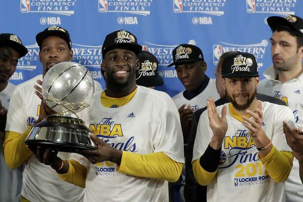 Golden State Warriors' Draymond Green carries the trophy as Kevin Durant, left rear, and Stephen Curry, front right, cheer after their 129-115 win over the San Antonio Spurs during the second half in Game 4 of the NBA basketball Western Conference finals, Monday, May 22, 2017, in San Antonio. (AP Photo/Eric Gay)