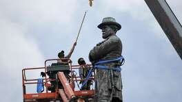 Workers on May 19 prepare to take down the statue of former Confederate general Robert E. Lee, which stands over 100 feet tall, in Lee Circle in New Orleans. The city's mayor, Mitch Landrieu, sparked controversy for removing four Confederate statues.