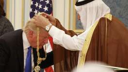 Saudi King Salman presents President Donald Trump with the highest civilian honor, the Collar of Abdulaziz Al Saud, at the Royal Court Palace on May 20, in Riyadh, Saudi Arabia. In his first foreign trip, Trump clearly aligned the U.S. with the Sunni Muslim countries.