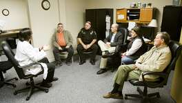 Dr. William Cooke, far left, speaks during a meeting with local and state officials about the recent HIV outbreak in Scott County at Foundations Family Medicine in downtown Austin, Ind., in 2015. Cooke is administering to a community beset by rampant opioid use.