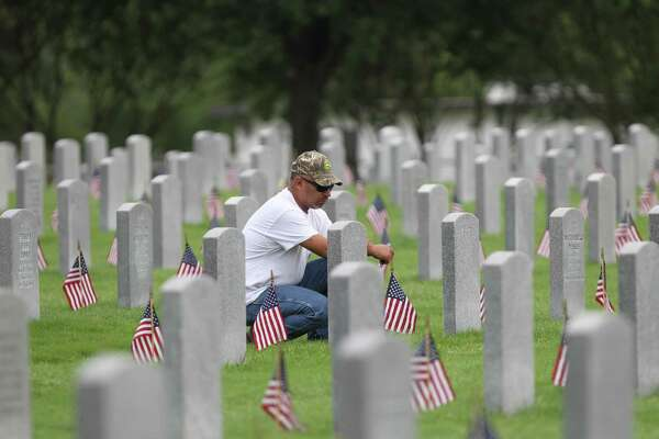 Jason Vasquez pays his respect at the grave of his father at the Houston National Cemetery before a Memorial Day Service, honoring deceased United States servicemen and women Monday, May 30, 2016, in Houston. This is a day we must also remember those who came back — honoring them best by giving them the services they need.