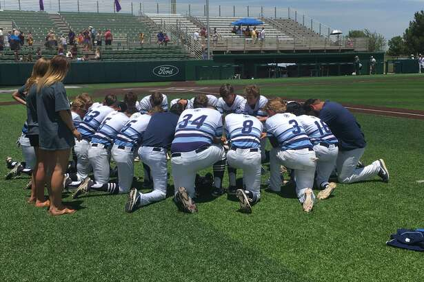 Greenwood baseball players and coaches pray together after their 2-1 loss against Godley in eight innings, in a Class 4A regional semifinal game on Friday at Abilene Christian University's Crutcher Scott Field. Photo by Will Korn