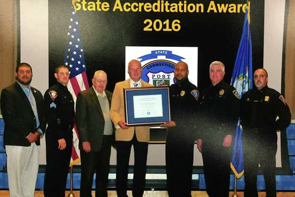 Mayor Mark Lauretti and Acting Police Chief Shawn Sequeira hold the accreditation awarded to the Shelton Police Department. Board of Aldermen President John Anglace is on Lauretti's immediate left.